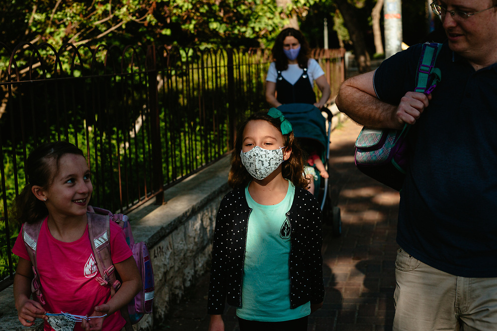 Twin girls Alma (C) and Clil (L), their brother Ofek, and parents Anna and Matti Michel, are seen as they walk towards the elementary school where the girls study in Jerusalem, Israel, on May 3, 2020.