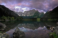 """This is the upper lake (of two) of Fusine Valromana nearby Tarvisio in Friuli, Italy, almost certainly one of the best spot of the Giulian Alps, right at the border with Austria and Slovenia. Mount Mangart is the name of the range in the background..I love the contrast here between the stormy sky and the perfectly still waters of the lake. Taken about 45 minutes after sunset, this is stitched from six vertical takes of 30"""" @f11 each."""