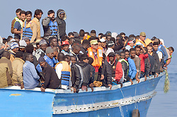 Migrants stranded on a boat, thirty miles off the Libyan coast as they are rescued by Royal Marines.