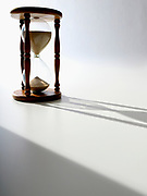 Side lit photo of an hourglass with shadow falling across the table