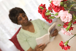 Older woman sitting reading a book,
