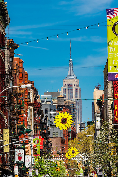 Mulberry Street in Little Italy with Empire State Building in background, New York, New York USA.