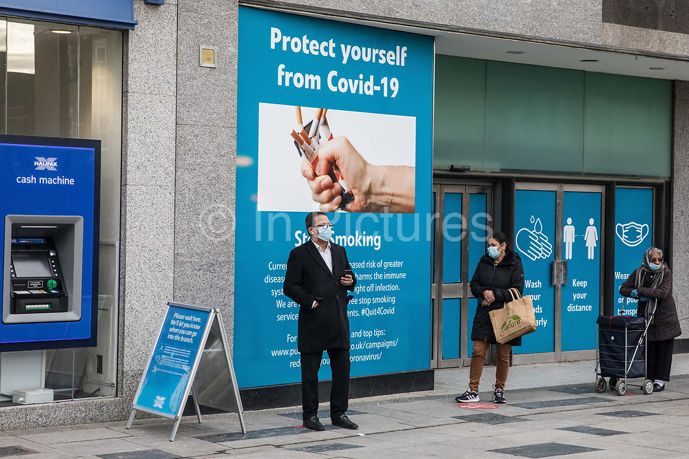 Members of the public wear face coverings as they queue to enter a branch of a building society on 26th November 2020 in Slough, United Kingdom. The UK government has announced that Slough will move into Tier 3, the highest tier of coronavirus restrictions, when the second lockdown imposed to help prevent the spread of COVID-19 ends after 2nd December.