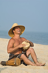 man enjoying playing with drums on the beach