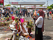 """12 JUNE 2020 - MINNEAPOLIS, MINNESOTA: Women photograph the impromptu memorial for George Floyd at the corner of 38th Street and Chicago Ave. in Minneapolis. The intersection is informally known as """"George Floyd Square"""" and is considered a """"police free zone."""" There are memorials to honor Black people killed by police and people providing free food at the intersection. Floyd, an unarmed Black man, was killed by Minneapolis police on May 25 when an officer kneeled on his neck for 8 minutes and 46 seconds. Floyd's death sparked weeks of ongoing protests and uprisings against police violence around the world.          PHOTO BY JACK KURTZ"""