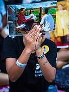 20 OCTOBER 2016 - BANGKOK, THAILAND:  A mourner on Sanam Luang holds up a photo of Bhumibol Adulyadej, the King of Thailand. Sanam Luang, the Royal Ceremonial Ground, is packed with people mourning the Monarch's death. The King died Oct. 13, 2016. He was 88. His death came after a period of failing health. Bhumibol Adulyadej was born in Cambridge, MA, on 5 December 1927. He was the ninth monarch of Thailand from the Chakri Dynasty and is also known as Rama IX. He became King on June 9, 1946 and served as King of Thailand for 70 years, 126 days. He was, at the time of his death, the world's longest-serving head of state and the longest-reigning monarch in Thai history.       PHOTO BY JACK KURTZ