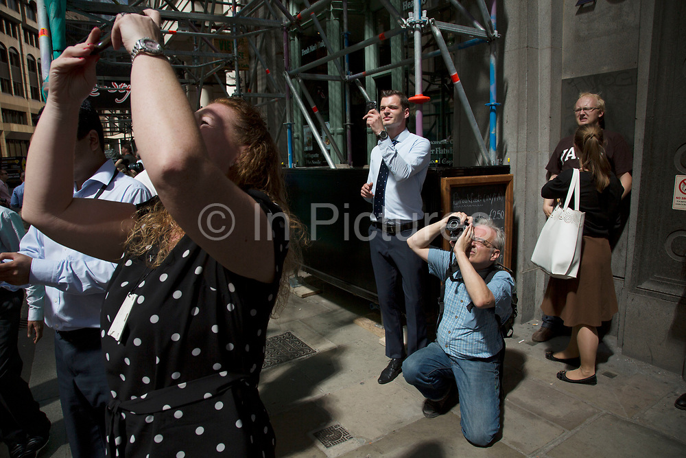 """London, UK. Wednesday 4th September 2013. People stop to watch and take pictures and experience the heat. Urgent action in planned to """"cover up"""" the Walkie Talkie skyscraper in the City after sunlight reflected from the building melted a car on the streets below. Temperatures have been measured in excess of 50 degrees C, and as much as 70 degrees at it's peak. The 525ft building has been renamed the """"Walkie Scorchie"""" after its distinctive concave surfaces reflected a dazzling beam of light which has caused extensive damage to nearby buildings."""