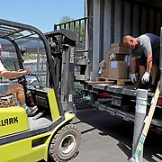 Bill Palmer (L) who owns Palmer Feed Store and delivery driver Andrew Randall unload a shipment of goods on Monday, March 30, 2020 in Orlando, Florida. The feed store sells livestock, pet food and live plants and has been very busy since the Coronavirus (Covid-19) threat as emerged. (Alex Menendez via AP)