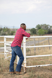 man leaning on a rustic fence looking off