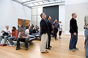 visitors to the museum of Modern Art in NYC reading a text on the wall
