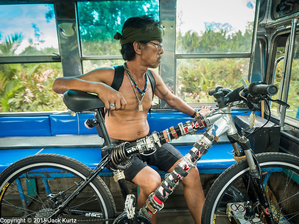"""13 MAY 2015 - MAHACHAI, SAMUT SAKHON, THAILAND: A passenger in a """"songthaew"""" running from Samut Sakhon to Samut Songkram. Songthaew means literally """"two rows."""" It is a passenger vehicle in Thailand and Laos adapted from a pick-up or a larger truck and used as a share taxi.    PHOTO BY JACK KURTZ"""