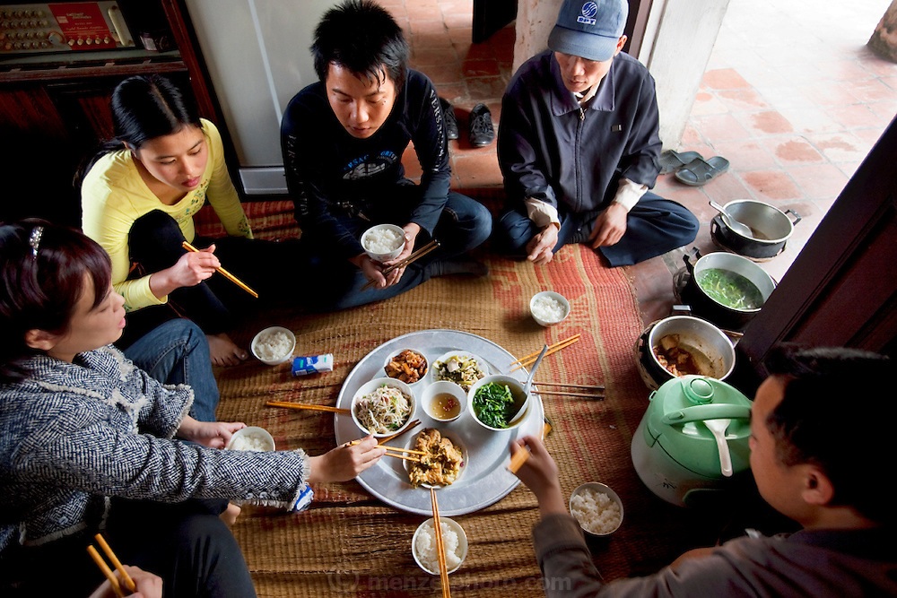 Rice farmer Theo Nguyen Van enjoys a meal with his family at his  home in Tho Quang Village, Vietnam. (From the book What I Eat: Around the World in 80 Diets.)