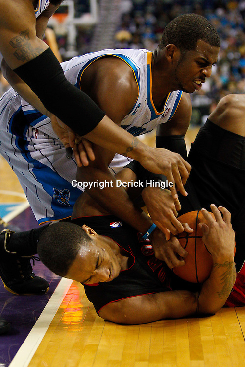 January 17, 2011; New Orleans, LA, USA; Toronto Raptors shooting guard DeMar DeRozan (10) and New Orleans Hornets point guard Chris Paul (3) fight over a loose ball during the third quarter at the New Orleans Arena.   Mandatory Credit: Derick E. Hingle