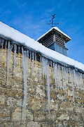 Weather vane and icicles on a barn in The Cotswolds