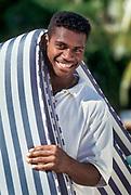Photo d'un jeune homme Kanak plagiste dans l'hôtel Le Méridien Ile des Pins avec des matelas sur l'épaule.