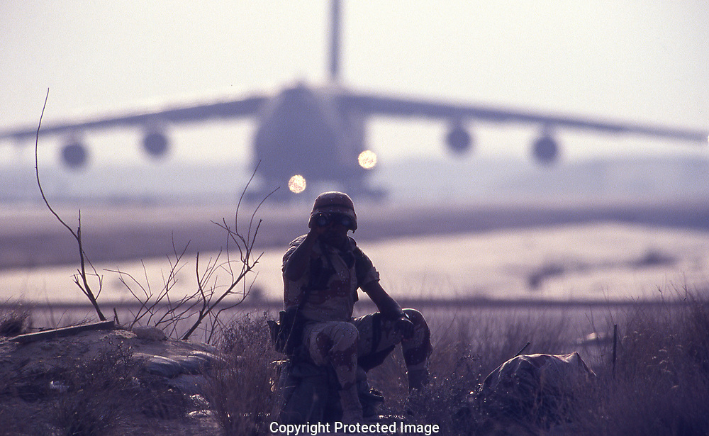 Gulf War One:    Sitting Guard. a sentry at the end of a runway at the air base in darahan. Saudi Arabia.  In the background is a C 5 A<br /><br />Photograph ny Dennis Brack. bb78