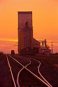 Grain elevator and rail tracks silhouetted against a sunset sky<br /> Wolseley<br /> Saskatchewan<br /> Canada