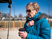 """20 MARCH 2020 - DES MOINES, IOWA: A woman waits in the cold for hand sanitizer at the Foundry, a distillery in Des Moines. The distillery suspended its distilling operations to make hand sanitizer this week. They distributed it free to people who came to their building. On Friday thousands of people came to get some. There line was more than one mile long. On Friday morning, 20 March, Iowa reported 45 confirmed cases of the Coronavirus. Restaurants, bars, movie theaters, places that draw crowds are closed for at least 30 days. There are no """"shelter in place"""" orders in effect anywhere in Iowa but people are being encouraged to practice """"social distancing"""" and many businesses are requiring or encouraging employees to telecommute.      PHOTO BY JACK KURTZ"""