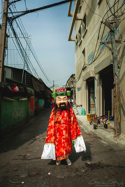 A man wearing a costume and mask celebrating Chinese New Year standing in an alleyway in the market, Pak Khlong Talat, Bangkok, Thailand