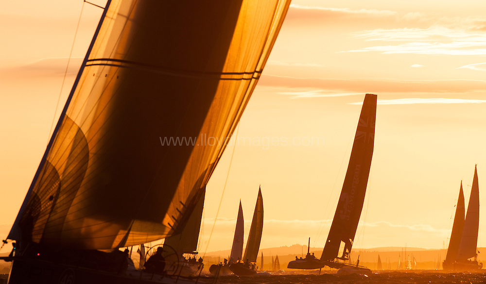 J.P.Morgan Asset Management Round the Island Race 2013. Pictures of the fleet crossing the start line as the sun rises this morning.