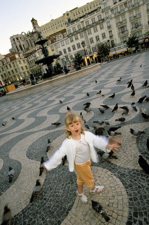 EU, Portugal, Lisbon. Girl (4 years) chases pigeons over wavy cobblestone design in Rossio Square. MR
