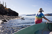 Liana Welty pulls a rowboat onto shore at small Isla Pitahaya in Bahia de Concepcion, Baja California Sur, Mexico. Many small islands are easily accessed from Playa Santispac and other beaches in the bay.