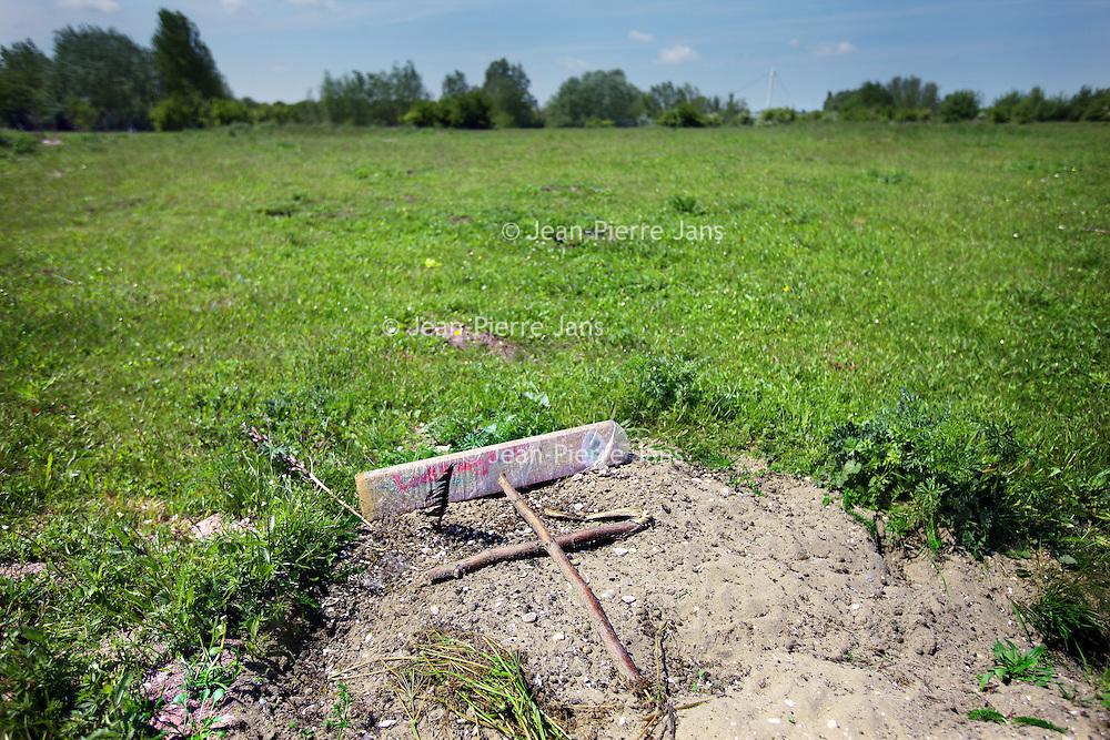 Nederland, Amsterdam , 31 mei 2013.<br /> In het Diemerpark is de laatste tijd Myxomatose bij konijnen vastgesteld.<br /> Myxomatose is een ernstige konijnenziekte met een sterfte van meer dan 90%.<br /> De laatste tijd hebben kinderen de dode konijnen veelvuldig begraven en schijnt het aantal dode konijnen als gevolg van deze  de ziekte te zijn afgenomen.<br /> Op de foto: 1 van de plekken waar kinderen de overleden konijnen hebben begraven vaak met een houten plank erbij met tekst erop geschreven van welk konijn en wanneer etc..<br /> In the Diemerpark (Amsterdam) the rabbits suffer from myxomatosis. Children burried a dead rabbit here and put a cross on its grave.