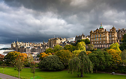 Edinburgh, Scotland, UK. 8 October 2020. Late afternoon sunshine and dark loudy skies adds drama to the skyline of the Old Town and Princes Street Gardens in Edinburgh.  Iain Masterton/Alamy Live News
