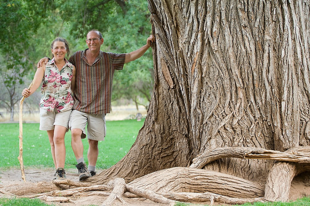 Hikers Liana and Parmenter Welty pose besides the trunk of the giant Fremont cottonwood tree (Populus fremontii) at the Zion Lodge in Zion National Park, Utah.