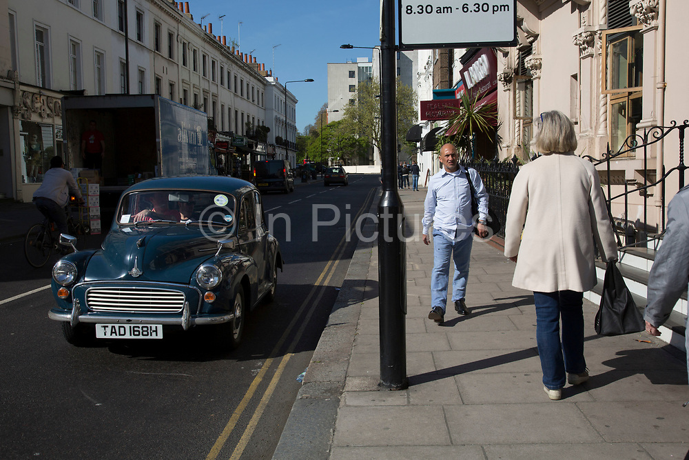 Street scene as a vintage Morris Minor car passes on Gloucester Road in Knightsbridge. In a selected few boroughs of West London, wealth has changed over the last couple of decades. Traditionally wealthy parts of town, have developed into new affluent playgrounds of the super rich. With influxes of foreign money in particular from the Middle-East. The UK capital is home to more multimillionaires than any other city in the world according to recent figures. Boasting a staggering 4,224 'ultra-high net worth' residents - people with a net worth of more than $30million, or £19.2million.. London, England, UK.