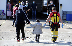 © Licensed to London News Pictures. 09/10/2021. Dungeness, UK. A young migrant is helped ashore by an RNLI volunteer at Dungeness in Kent after crossing the English Channel. Hundreds of migrants have made the crossing in the calm weather this week. Photo credit: Sean Aidan/LNP
