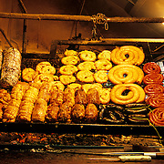 South America, Uruguay, Montevideo. Carniverous Uriguayans prepare for the lunch crowd at a geill in the Mercado Puerta.