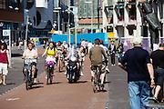 Nederland, Den Haag, 08-06-2014<br /> In Den Haag rijdt een man met een vrouw achterop op een bromscooter tussen de fietsers op de Grote Marktstraat, een belangrijke winkelstraat. Alleen fietsers en voetgangers mogen hier komen. <br /> <br /> In The Hague people cycle at the Grote Markstraat. Only bicycles and pedestrians are allowed in this street.