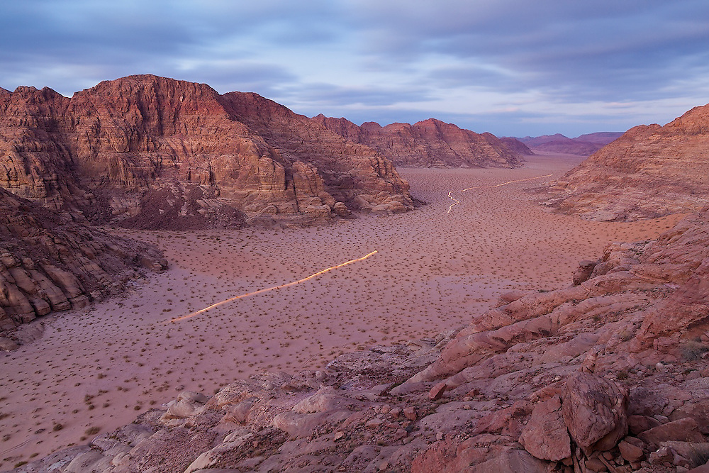 A jeep drives at dusk through the desert in Wadi Rum, Jordan.