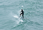 A man in a wet suit does stand up paddle surfing on a wave. Explore Pacific Ocean beaches and sea cliffs at Patrick's Point State Park, 25 miles (40 km) north of Eureka, California, USA.
