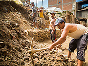 04 AUGUST 2015 - BUNGAMATI, NEPAL: Men dig out a residential street in Bungamati, a village about an hour from Kathmandu. Three months after the earthquake debris from the earthquake still clogs many of the streets in the community. The Nepal Earthquake on April 25, 2015, (also known as the Gorkha earthquake) killed more than 9,000 people and injured more than 23,000. It had a magnitude of 7.8. The epicenter was east of the district of Lamjung, and its hypocenter was at a depth of approximately 15 km (9.3 mi). It was the worst natural disaster to strike Nepal since the 1934 Nepal–Bihar earthquake. The earthquake triggered an avalanche on Mount Everest, killing at least 19. The earthquake also set off an avalanche in the Langtang valley, where 250 people were reported missing. Hundreds of thousands of people were made homeless with entire villages flattened across many districts of the country. Centuries-old buildings were destroyed at UNESCO World Heritage sites in the Kathmandu Valley, including some at the Kathmandu Durbar Square, the Patan Durbar Squar, the Bhaktapur Durbar Square, the Changu Narayan Temple and the Swayambhunath Stupa. Geophysicists and other experts had warned for decades that Nepal was vulnerable to a deadly earthquake, particularly because of its geology, urbanization, and architecture.    PHOTO BY JACK KURTZ