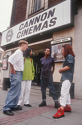 Multiracial group of teenagers standing outside cinema talking,