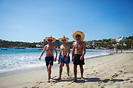 A group of friends from the U.K. and Ireland wear sombreros as they walk on the beach in Puerto Escondido, Mexico