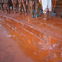 Workers line up for cleaning their protective suits and equipments in Devecser in Hungary's Veszprem county has been flooded by toxic sludge released by a dam accident in a nearby container. The toxic chemicals left its red marking on all the walls of the houses in and out and covered all moveable belongings and streets killing people and animals. Red sludge is a waste from bauxite fefining that has a strong caustic effect. The toxic flood covered an area of over 800-1,000 hectares (1,920-2,400 acres). Seven people were killed and more than 150 injured in the disaster. Pollution from the red sludge now spread into the local rivers killing all life in rivers Marcal and Torna and now it mixed into the main European waterway river Danube. Officials say there is no risk of a biological or enviromental catastrophe there.  Devecscer, Hungary, Saturday, 09. October 2010. ATTILA VOLGYI