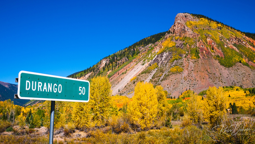 Fall color and road sign on the Million Dollar Highway near Silverton, San Juan National Forest, Colorado USA