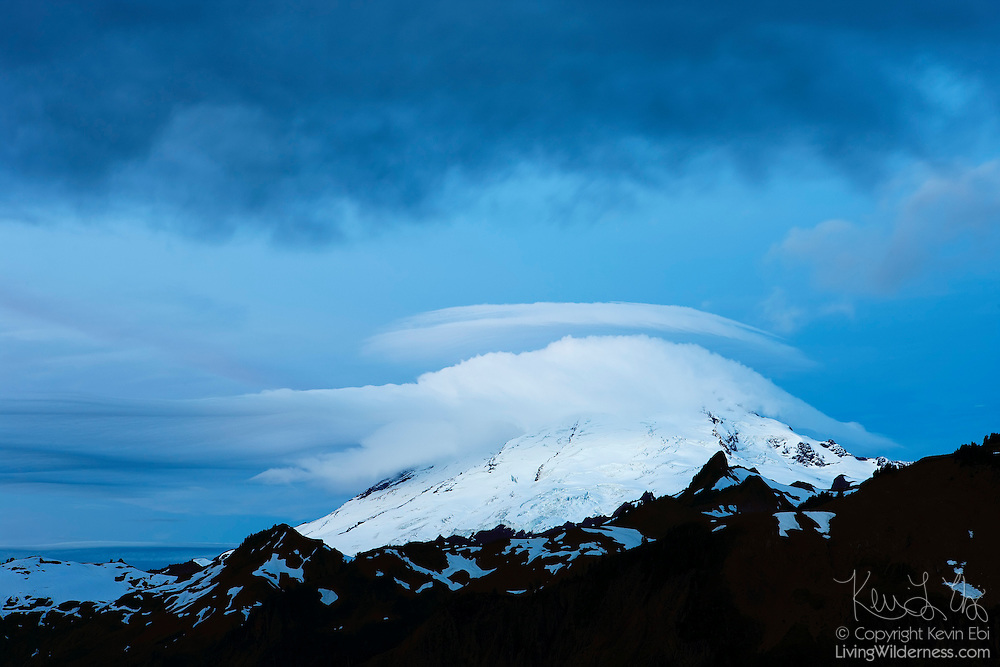 A cap cloud covers the summit of Mount Baker, a 10,778 feet (3,285 m) volcano in Washington state. Cap clouds, technically called orographic stratiform clouds, form when moist air is forced over a mountaintop. The moisture condenses into water droplets as it climbs in elevation.