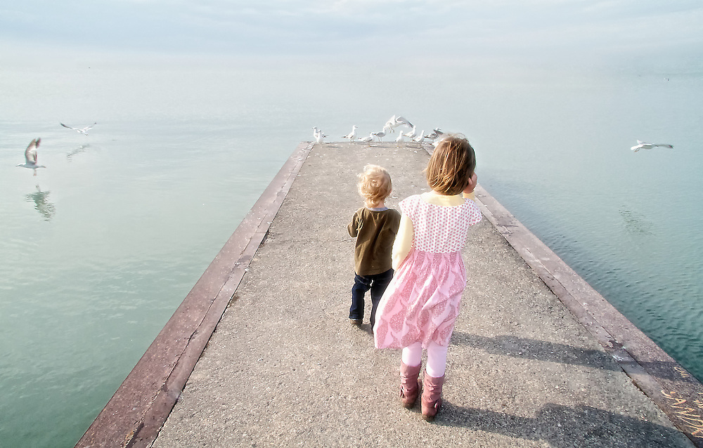 A boy and girl approach seagulls at the end of a pier situated on Lake Ontario, Toronto Canada.