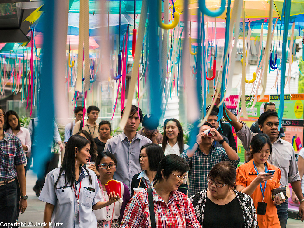 11 JUNE 2013 - BANGKOK, THAILAND: Shoppers walk under a display of umbrellas hanging in the entrance to the Terminal 21 shopping mall at the Asoke intersection in Bangkok.     PHOTO BY JACK KURTZ