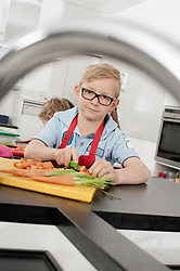 Two schoolboys cutting vegetables in home economics class, Bavaria, Germany