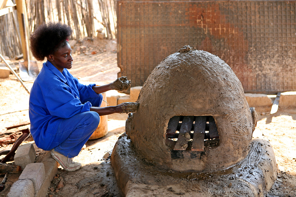 Africa, Namibia, Windhoek. A young underpriveleged woman employed at Penduka development cooperation organization in Namibia repairs cracks in a traditional clay oven.