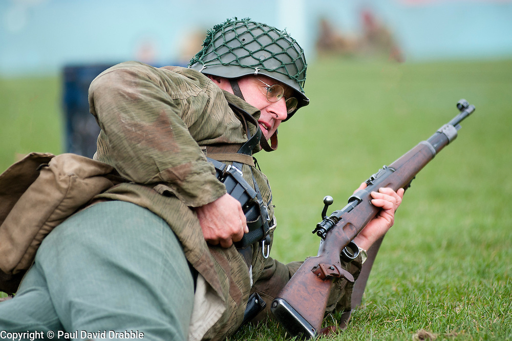 Reeactor portraying Panzer Grenadier from the 21st Panzer division reaches for his ammunition pouch to reaload his Mauser K98 rifle..21 April  2013.Image © Paul David Drabble