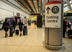© Licensed to London News Pictures. 17/01/2021. London, UK. Cabin crew walk past a Testing Centre sign at London Heathrow.  Passengers arriving from abroad on Monday morning will have to show that they have had a negative Covid-19 test. Today, Foreign Secretary Dominic Rabb, said that lockdown could be lifted in March but with tier systems in place as health chiefs reveal that a 24/7 vaccination pilot will begin next week as total Covid-19 deaths reach over 88,000 this weekend. Photo credit: Alex Lentati/LNP