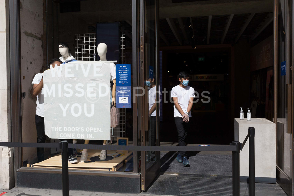 As the UKs Coronavirus lockdown continues to ease, retailers re-open their doors to shoppers, an employee of a Levis shop on Regent Street awaits customers with hand sanitiser dispensers, and another unpeels the sticky stencil lettering telling customers that their business has been missed, on 18th June 2020, in London, England.
