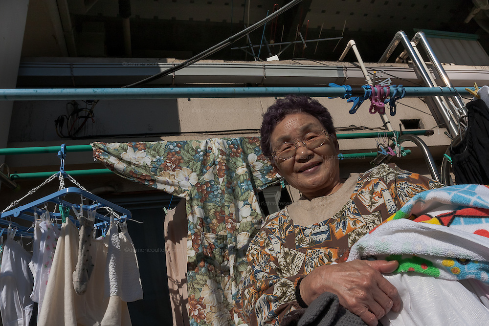 An older Japanese woman collect laundry outside her house that is built under the arches of  an expressway overpass in Hiroo, Tokyo, Japan. Friday February 3rd 2012
