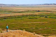 Boy overlooking prairie grasslands<br />